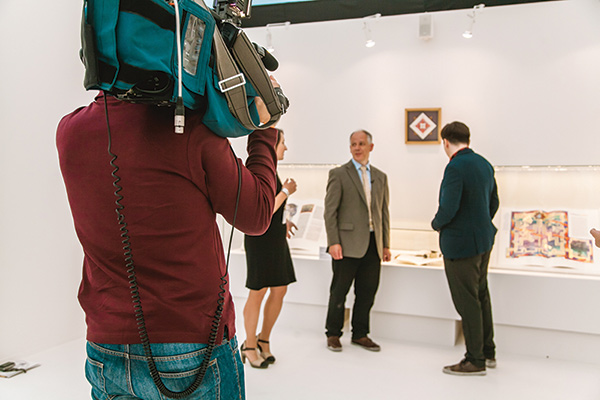 Тимоти Ноуд дает интервью (с переводчиком) московскому телеканалу перед стендом, на котором представлены его работы и работы Дональда Джексона.