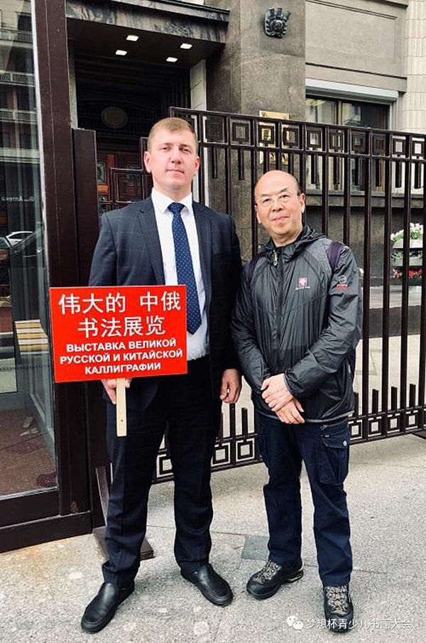 """5月28日华奎先生在俄罗斯杜马门前与""""伟大的中俄书法展览""""迎宾小伙合影留念"""