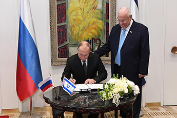 The President of Russia Vladimir Putin makes a record in the handwritten Guestbook of the Israeli President